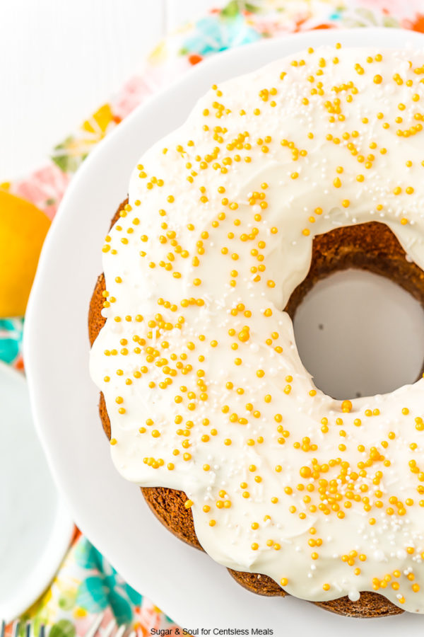 Overhead shot of a bundt cake with white icing and gold sprinkles on a white cake stand.