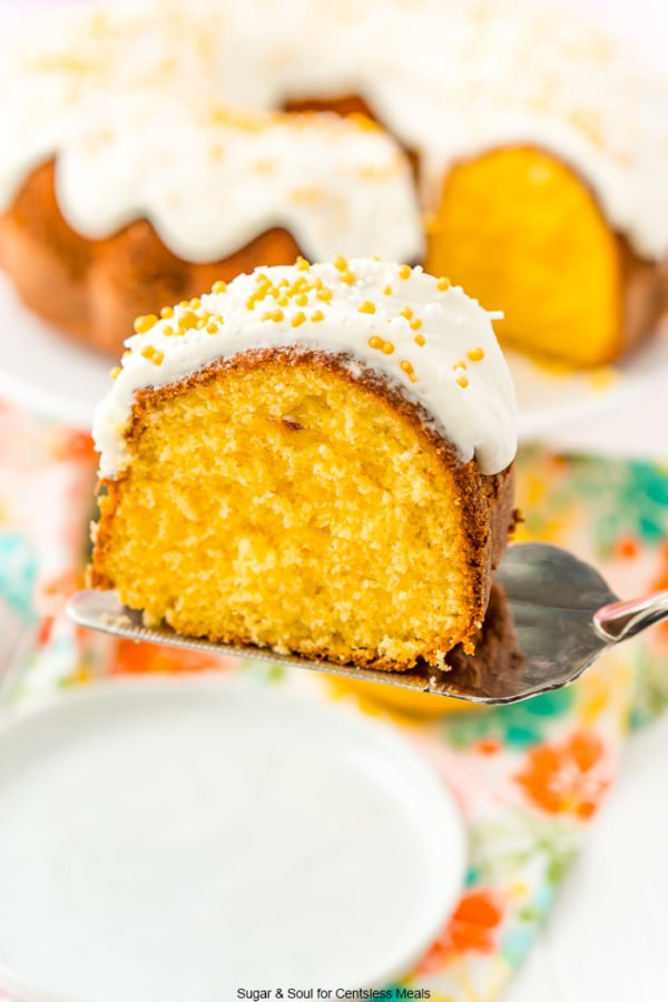 Slice of orange cake on a cake serving getting ready to be set on a white plate.