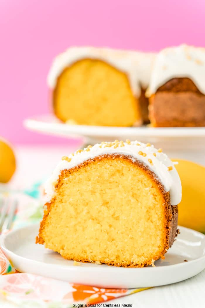 Slice of orange bundt cake on a white plate with a pink background and more cake on a cake stand.