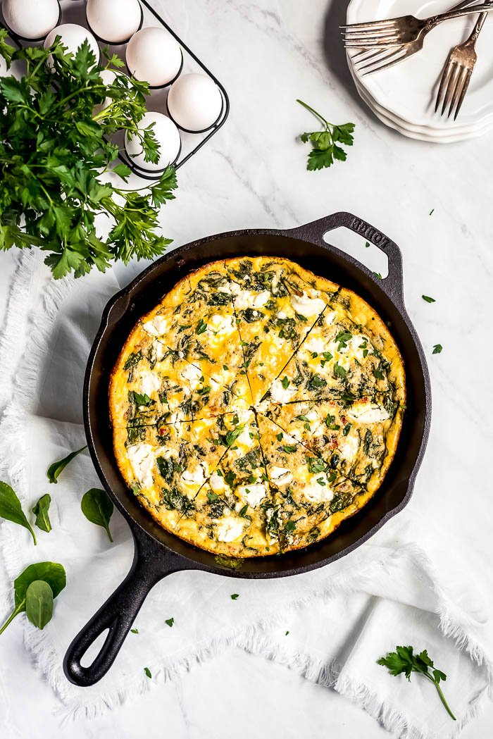 Spinach Frittata in a cast iron skillet with spinach leaves, parsley, and whole eggs on the side.