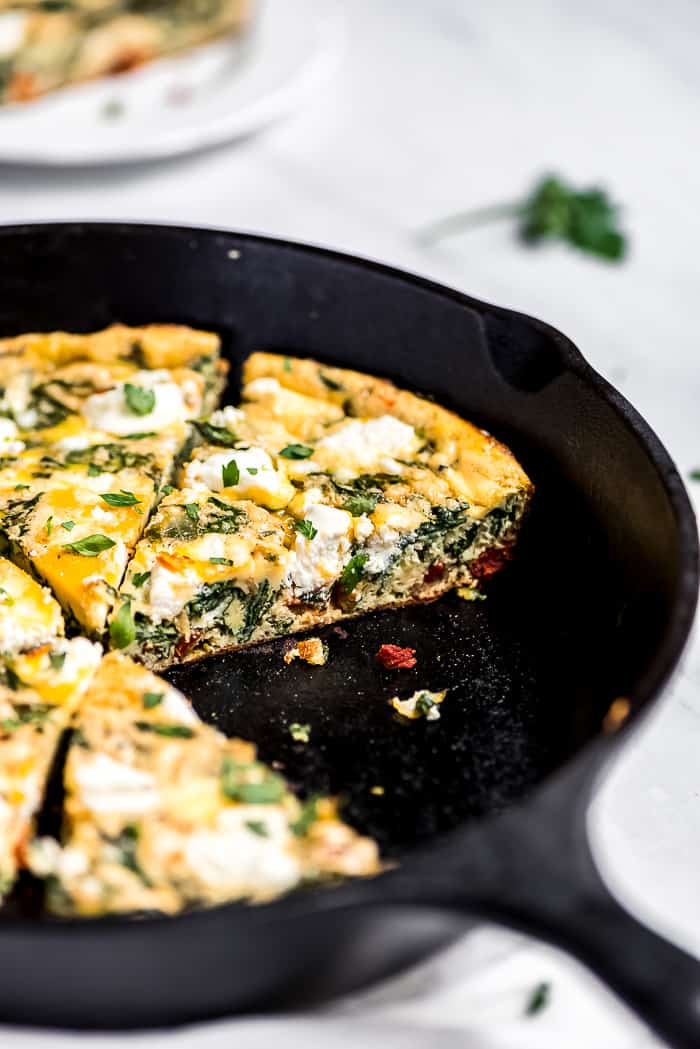 Close up of Spinach Frittata in a cast iron skillet showing spinach and goat cheese.