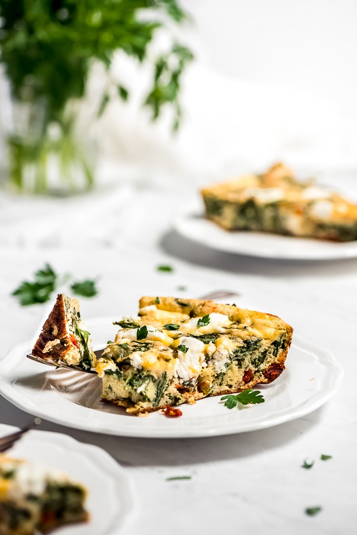 A slice of Spinach Frittata on a plate with a fork full of it on the side.