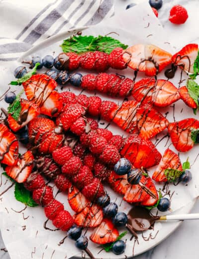 Fruit kabobs on a white plate drizzled with chocolate