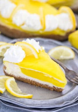 Piece of lemon cheesecake on a plate with a fork and lemon slices