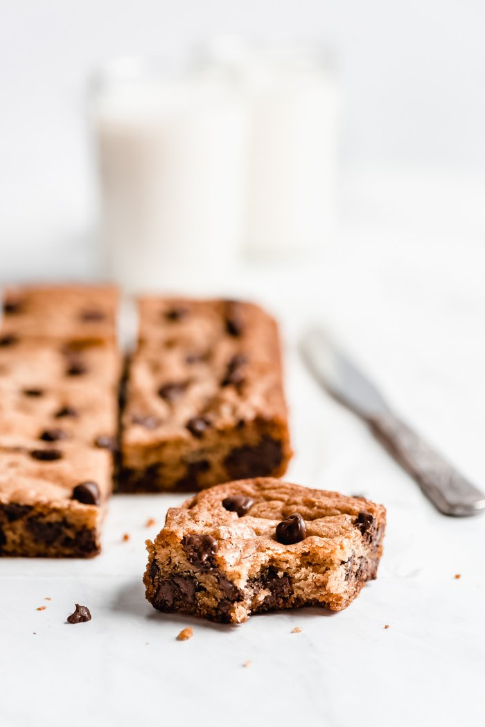 A chocolate chip cookie bar with a bite taken out to show the chewy texture.