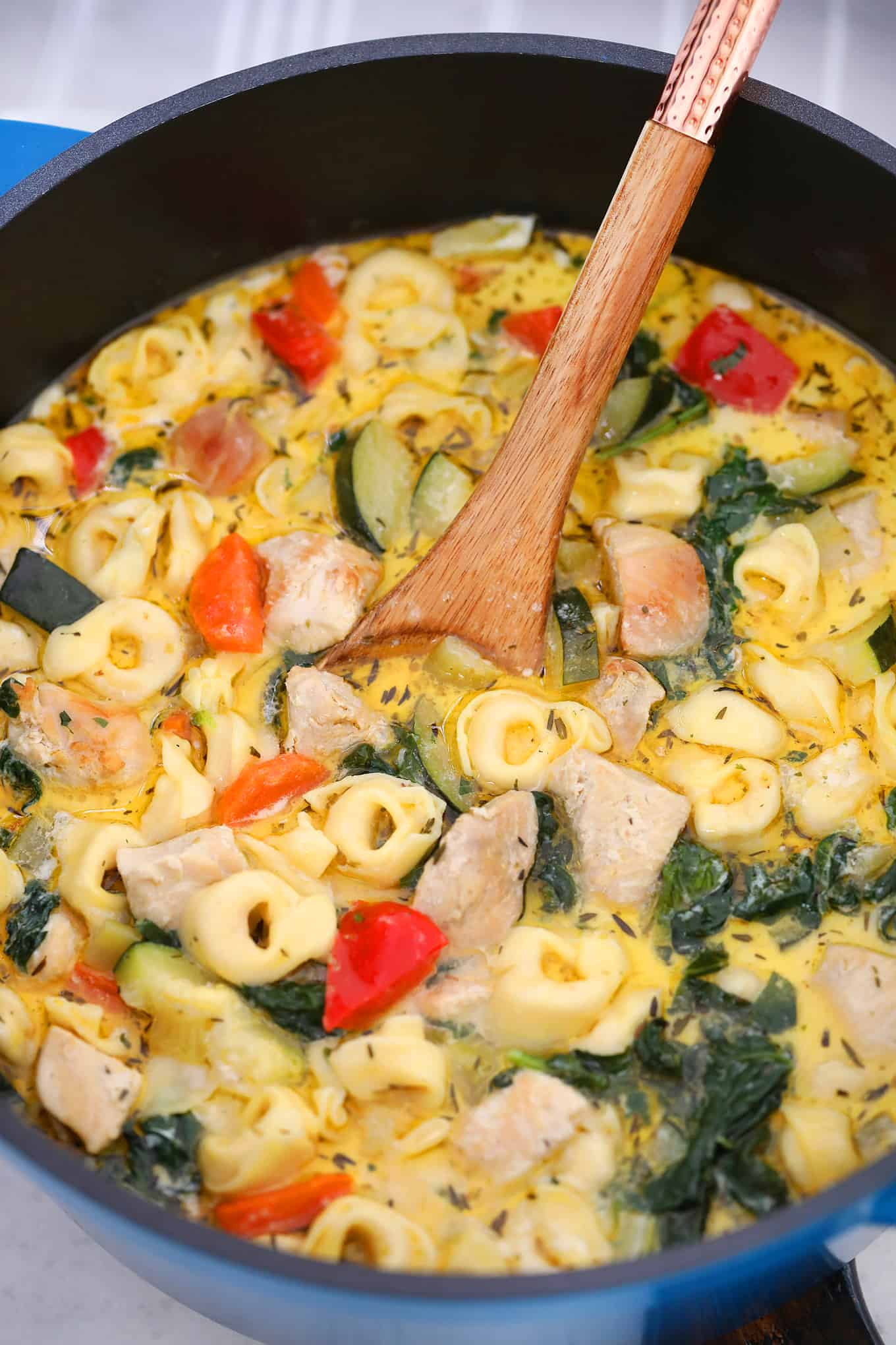 Chicken Tortellini Soup in a pot with a wooden spoon