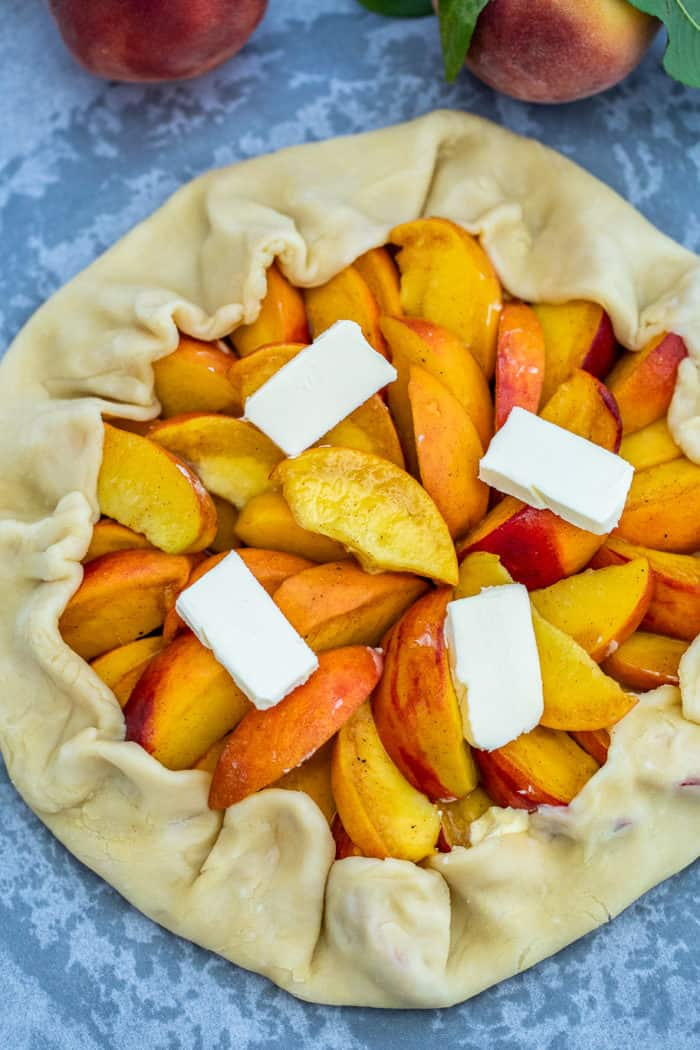 Peach Galette crust stuffed with peaches and topped with butter pats on top.