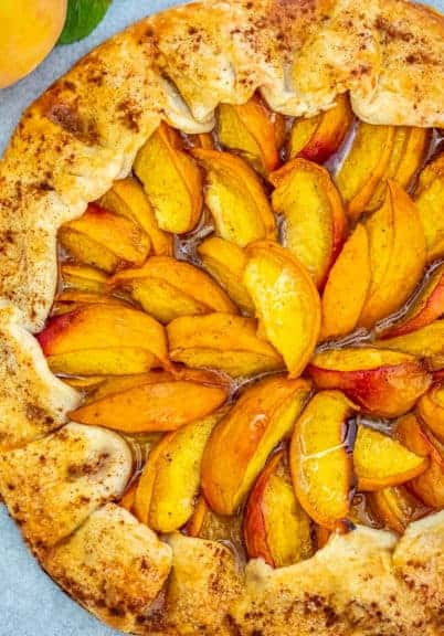 Peach Galette on a marble board with a peach on the side