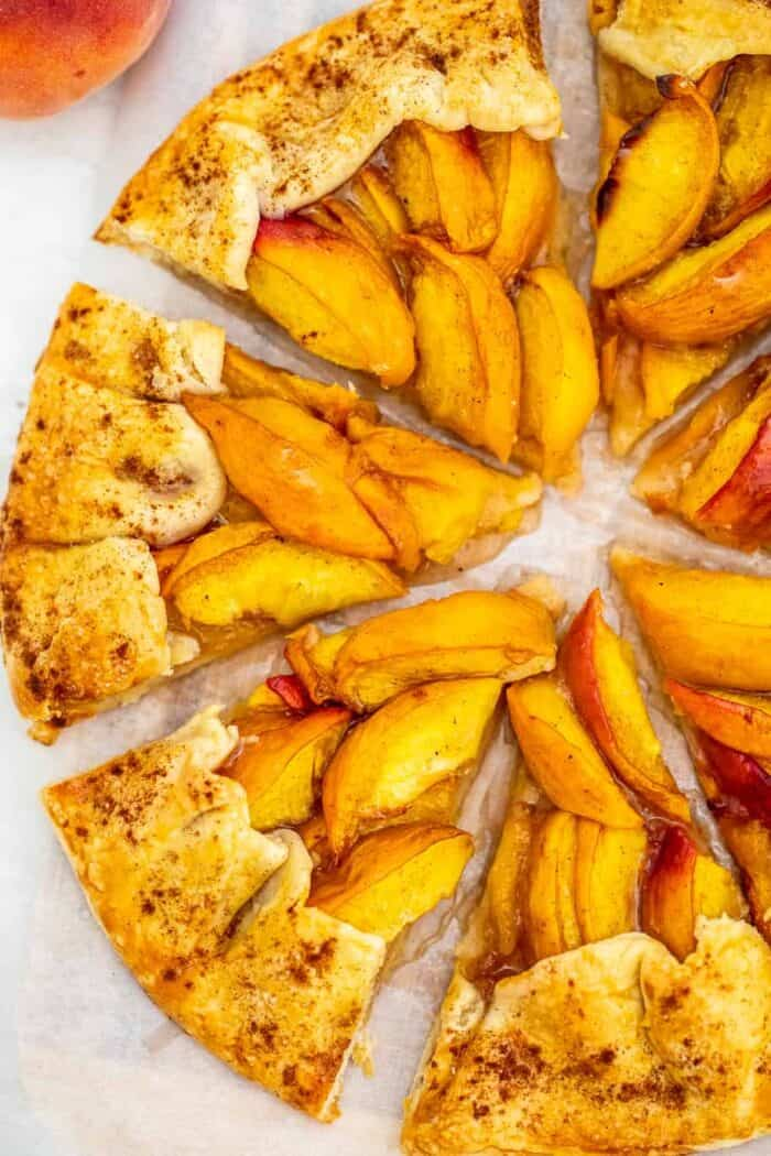 Peach galette sliced on a serving tray.