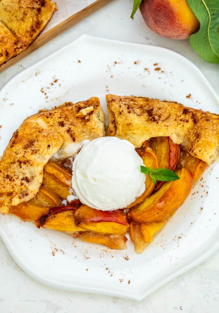Two slices of peach galette on a plate, topped with ice cream.