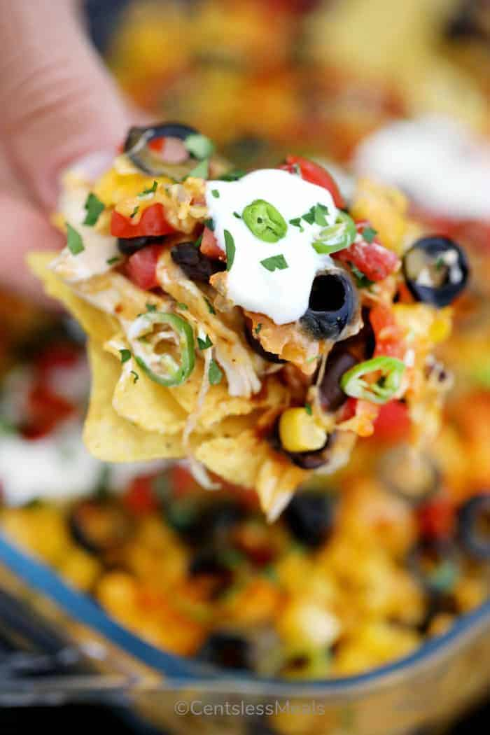 A serving of nachos being scooped up