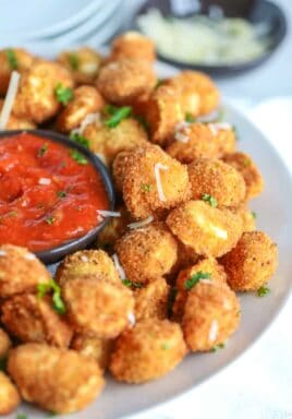 Crispy fried tortellini on a white plate with marinara sauce