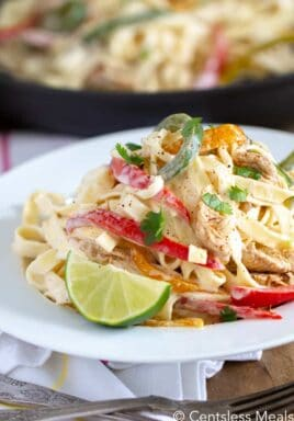 Fajita pasta on a white plate with a lime wedge