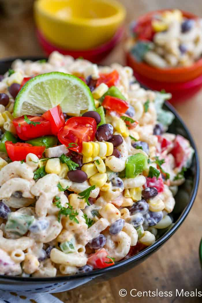 Southwestern macaroni salad in a bowl with a lime wedge and cilantro