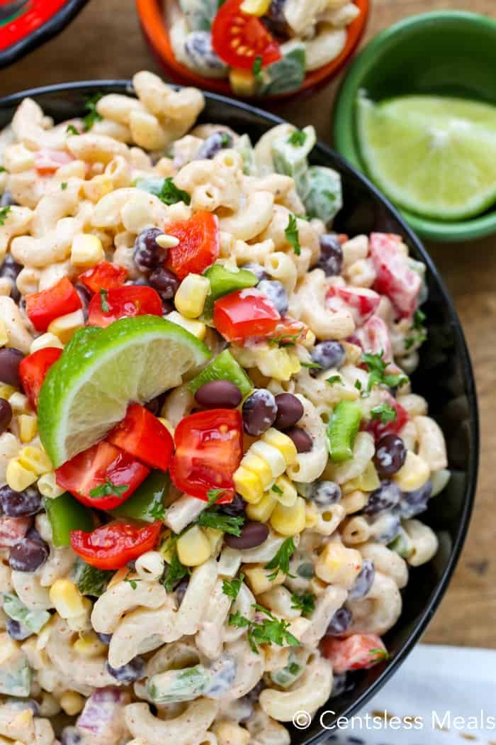 Southwestern macaroni salad in a black bowl with tomato and lime as garnish
