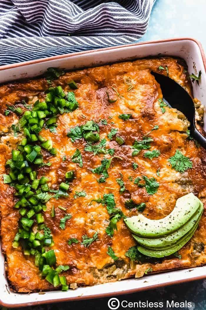 Chili rellano casserole in a casserole dish topped with green pepper and avocado