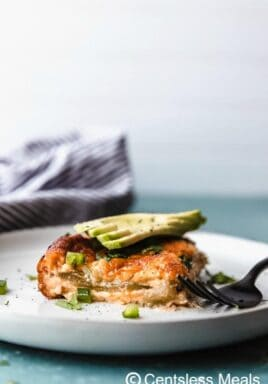 Chile relleno casserole on a white plate with avocado and a fork