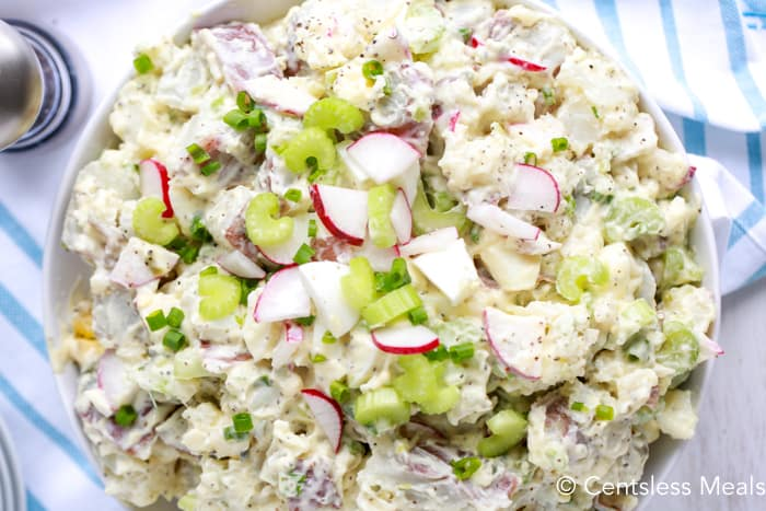 Creamy potato salad in a bowl garnished with green onions celery and radishes