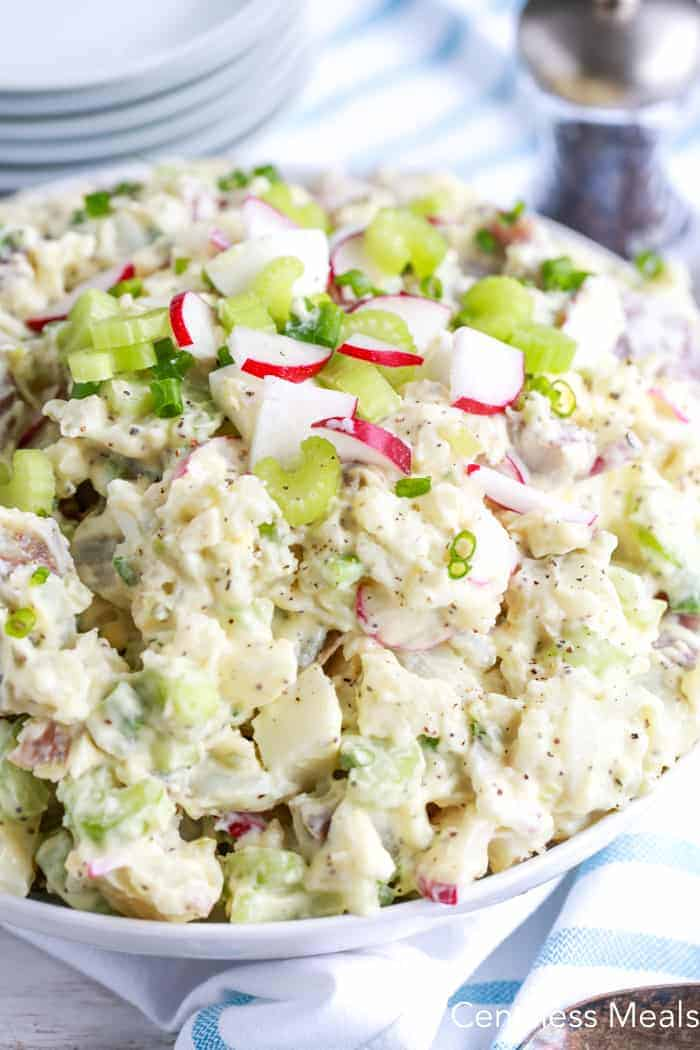 Creamy potato salad in a white bowl garnished with radishes and celery