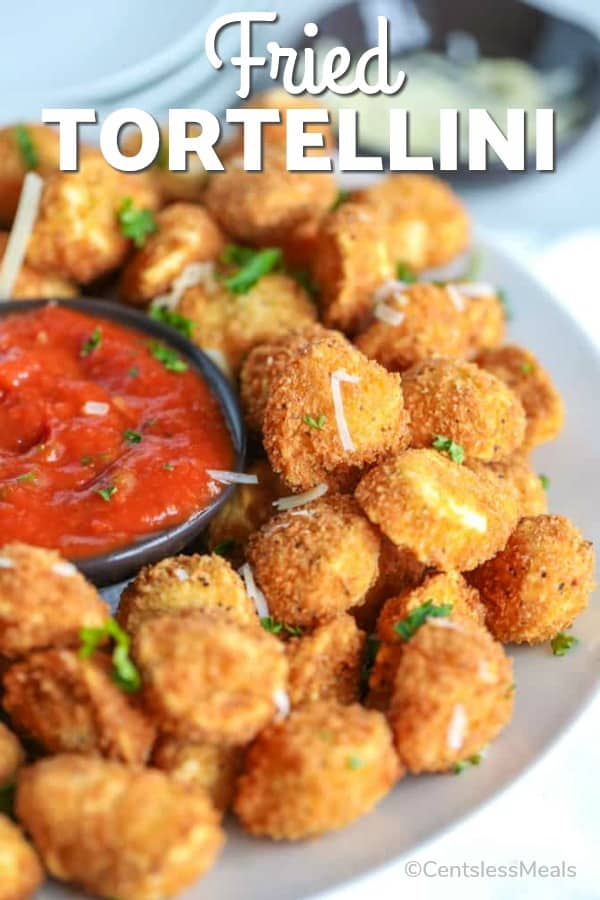 Fried tortellini on a plate with sauce and writing