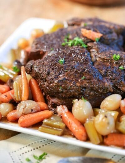 Slow cooker pot roast on a plate with veggies and parsley