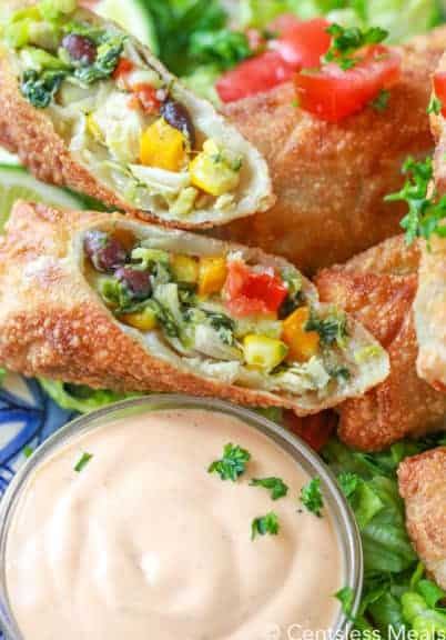 Avocado egg rolls on a plate with dip in a glass bowl