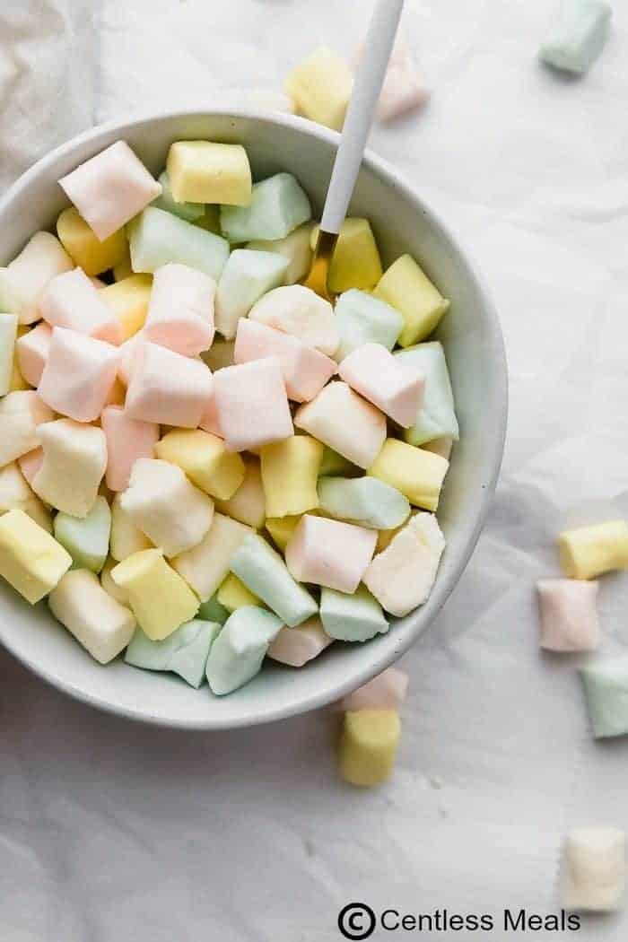 A white bowl filled with mints with a white bowls for serving on a light background