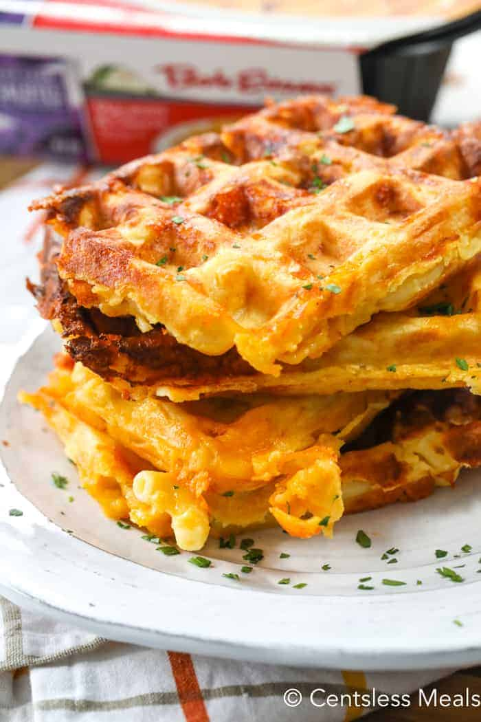 Mac and cheese waffles piled up together on a white plate and garnished with parsley.
