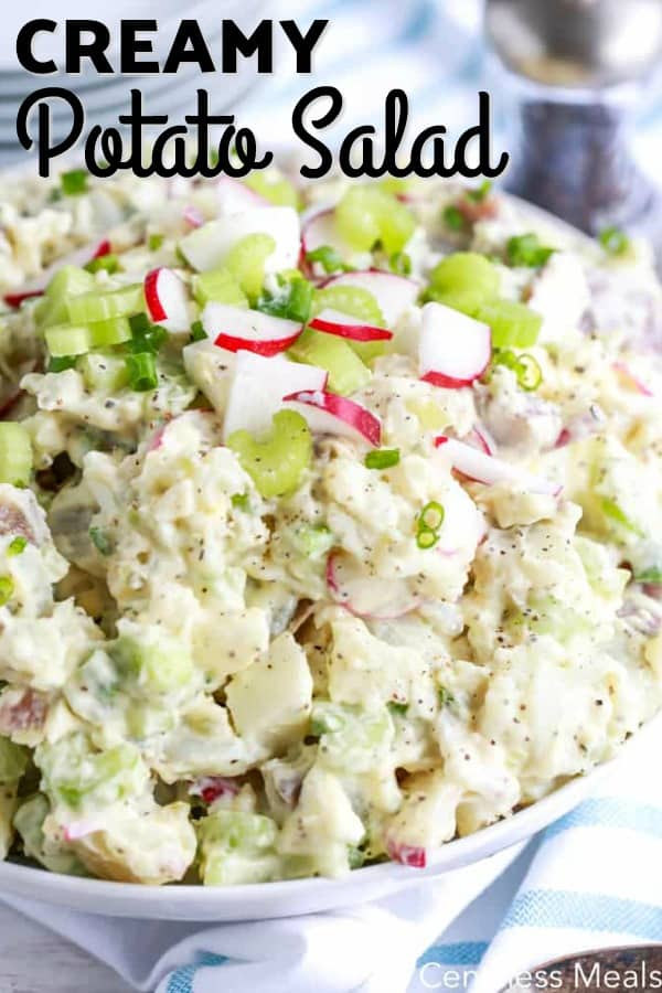 Creamy potato salad in a white bowl with writing