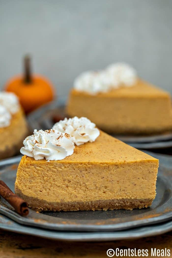 Pieces of pumpkin cheesecake on plates with whipped cream