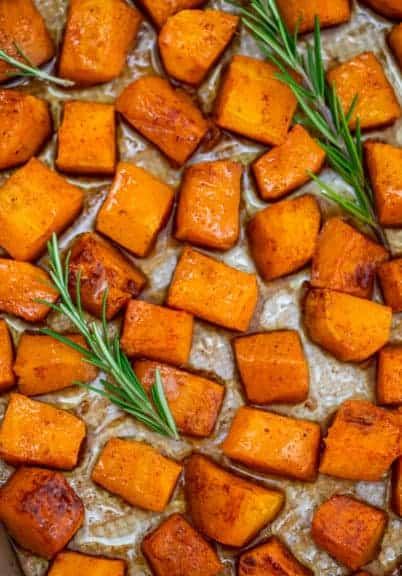 Roasted butternut squash on a baking sheet with rosemary Sprigs