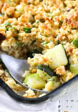 Stuffing zucchini casserole in a clear casserole dish with a spoon