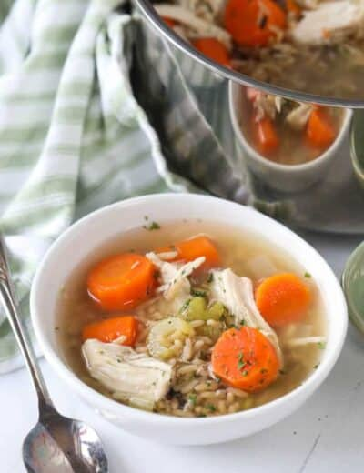 Chicken rice soup in a white bowl with a spoon and the pot of soup on the side