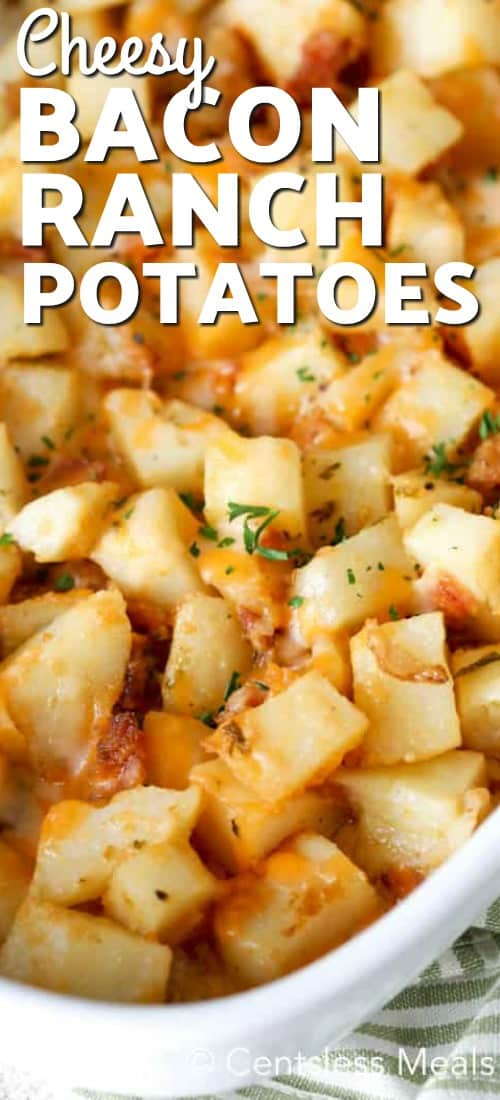 Cheesy Bacon Ranch Potatoes baked in a white casserole dish.