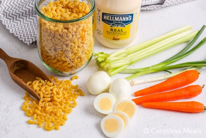 ingredients for macaroni salad with egg on a white board.