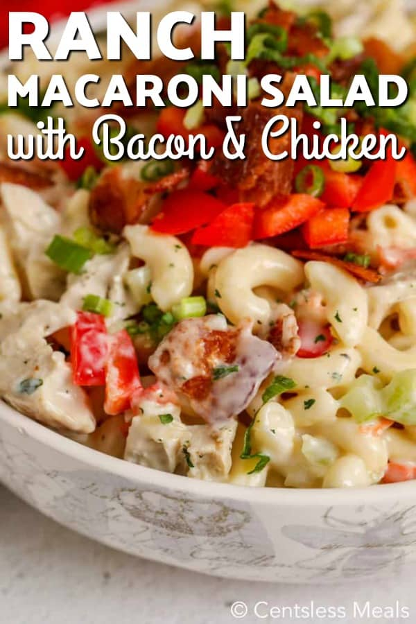 A bowl of ranch macaroni salad garnished with crisp bacon and green onions.