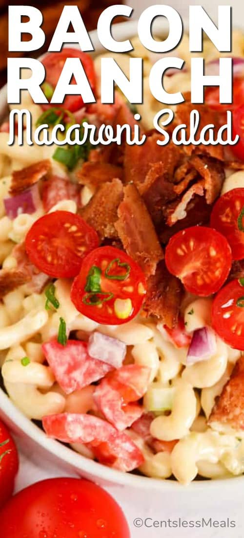 A close up of bacon ranch macaroni salad, garnished with bacon, tomatoes and green onions.