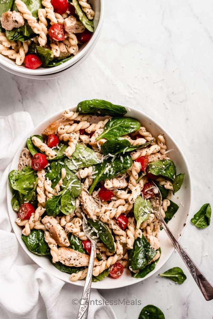 Spinach and Tomato Chicken Pasta Salad served in a white bowl with two silver spoons, garnished which parmesan cheese.