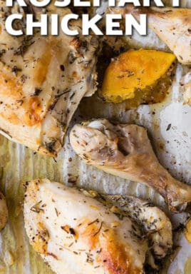 Oven Baked Rosemary Chicken pieces on parchment paper baked with lemons.