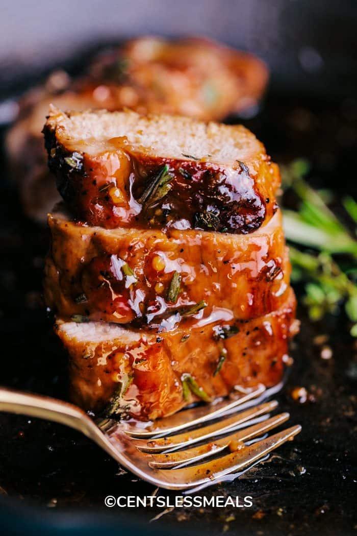 Honey Garlic Roasted Pork Tenderloin sliced and stacked in the skillet