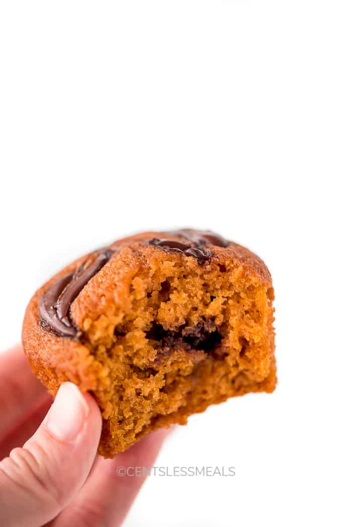 A hand holding a Nutella Pumpkin Muffin with a bite taken out of it