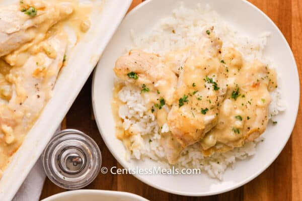 Creamy Chicken on a white plate with rice and parsley