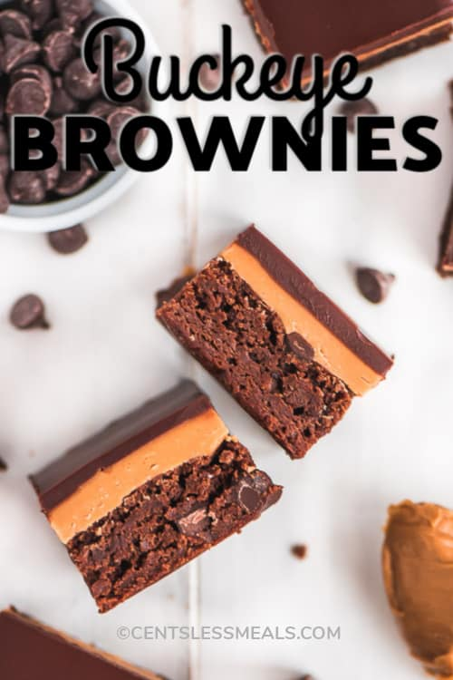 Buckeye Brownies spread out on a white surface with chocolate chips and a spoonful of peanut butter, with writing.