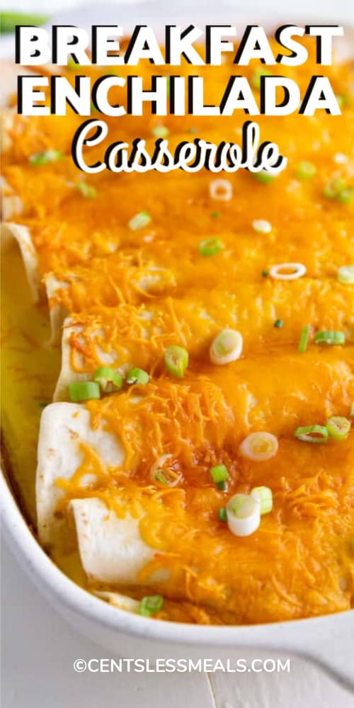 Breakfast Enchiladas garnished with green onion and baked in a white casserole dish with writing