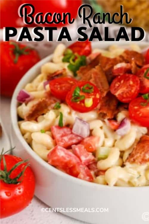 Ranch Pasta Salad with bacon and tomatoes in a white bowl, with writing.