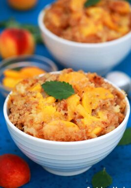 Peach Dump Cake in served in white bowls.
