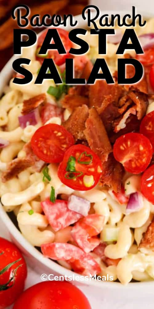 Bacon Ranch Pasta Salad in a white bowl, garnished with tomatoes, bacon and green onion, with a title.