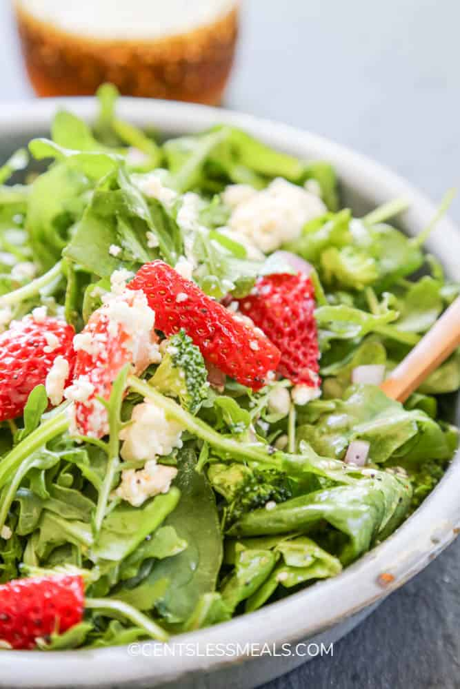 Spinach and strawberry salad in a bowl topped with cheese