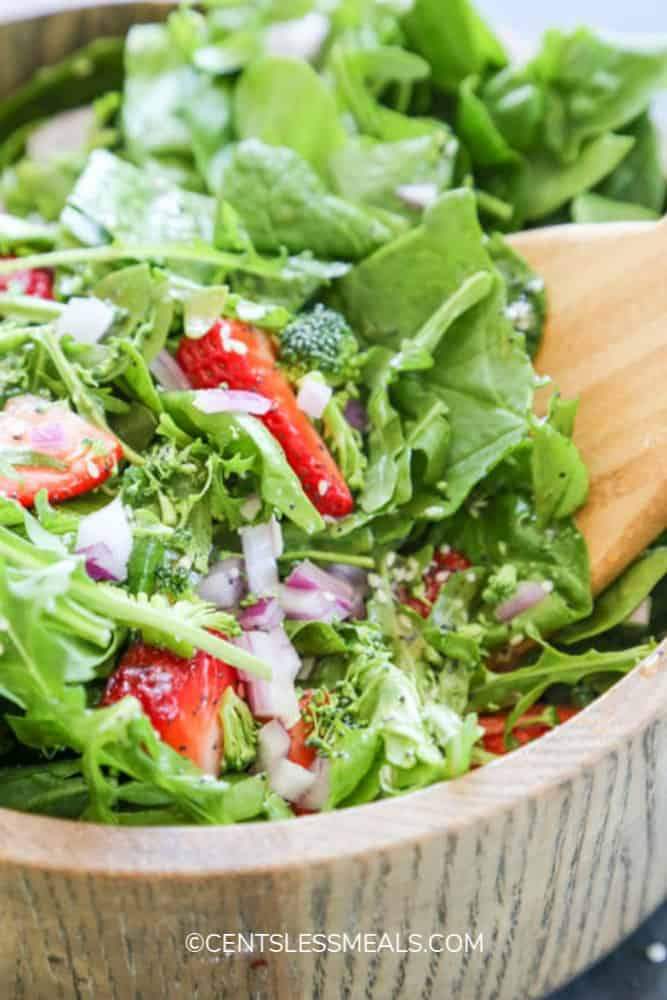 Spinach and strawberry salad in a wooden bowl with a wooden utensil