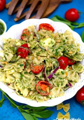 Caprese pasta salad in a white serving bowl with cherry tomatoes and basil beside.